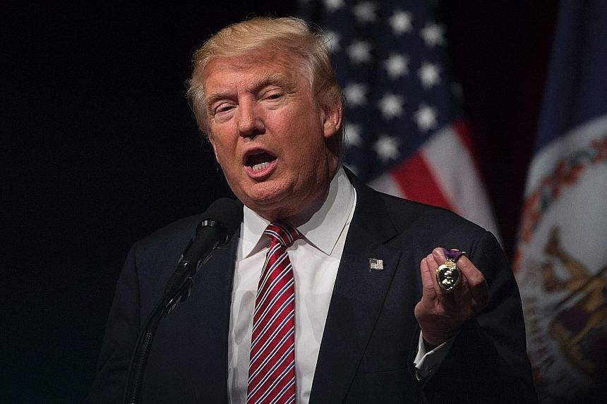 Mr Trump holding a Purple Heart medal, given to him by a veteran, during a rally in Virginia on Tuesday. The Republican presidential nominee has never served in the military.