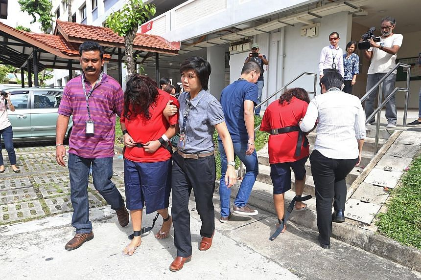 Police officers taking Gaiyathiri (left) and her mother Prema to their home in Bishan for investigations yesterday. The two women are accused of killing their Myanmar maid, Ms Piang Ngaih Don, some time between July 25 and 26. They were arrested last