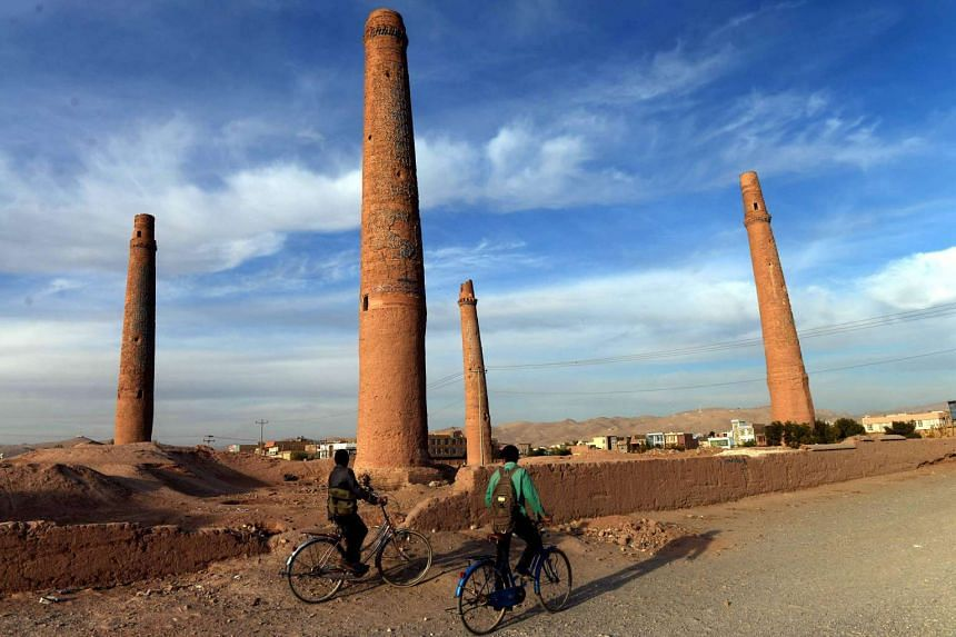 Afghan youths ride their bicycles past the historic minarets of Herat province in a 2014 file photo.