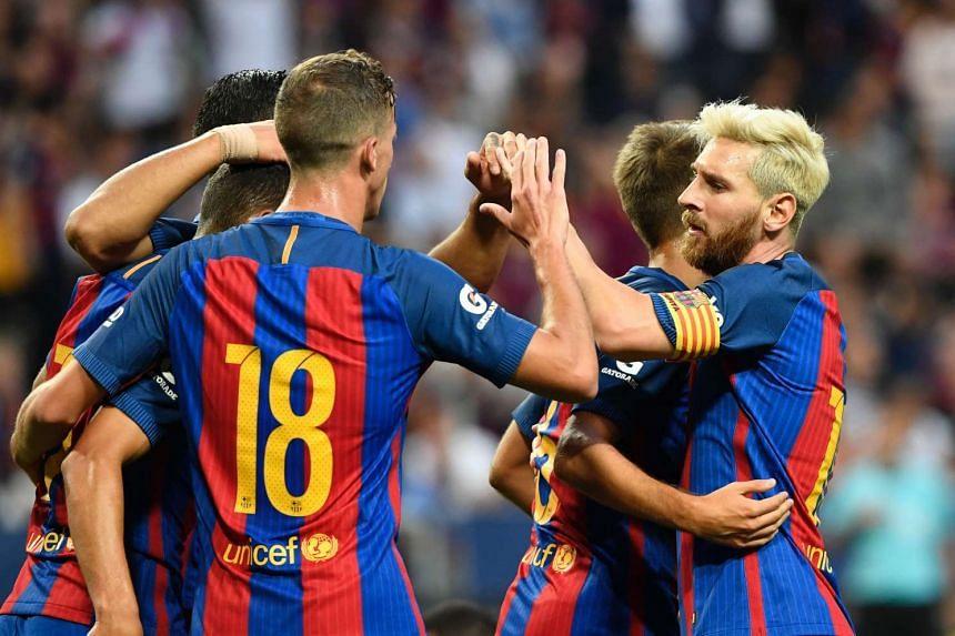 Barcelona forward Munir El Haddadi (left) celebrates with teammates Jordi Alba (centre) and Argentinian forward Lionel Messi after scoring.