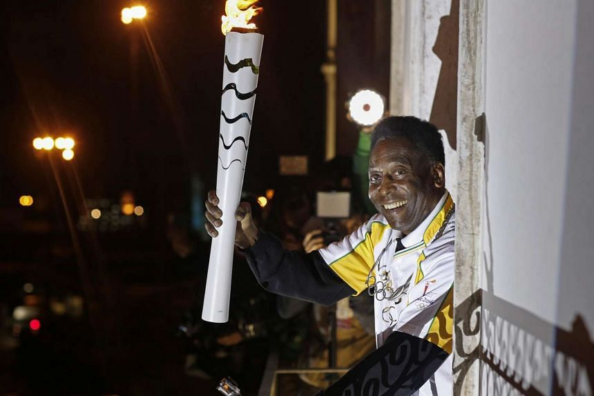 Pele holding the Olympic flame at the Pele Museum in Santos, Brazil.