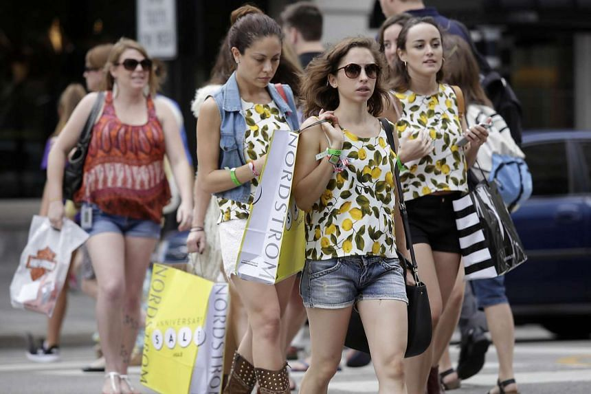 Consumers hold shopping bags as they walk along Michigan Avenue on July 29 in Chicago, Illinois.