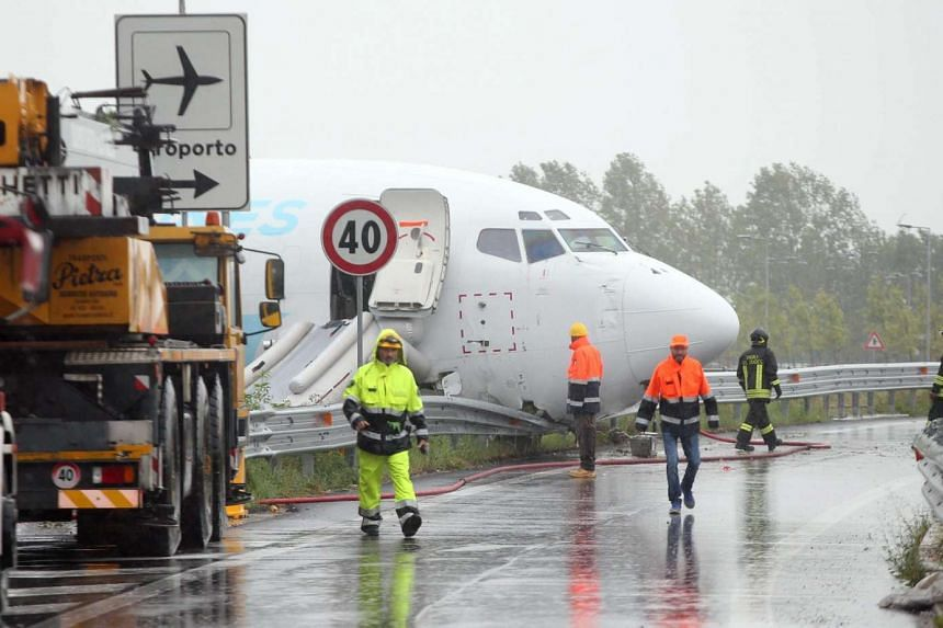The DHL courier company's Boeing 737-400 cargo aircraft rests on a road after it came off the runway after landing at the airport of Bergamo Orio al Serio on Aug 5, 2016.