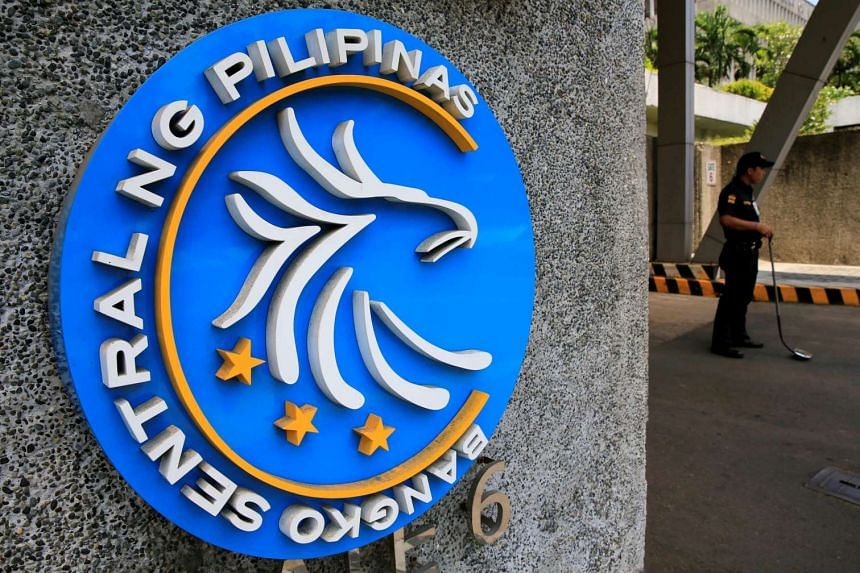 A security guard stands beside a logo of the Central Bank of the Philippines in Manila.