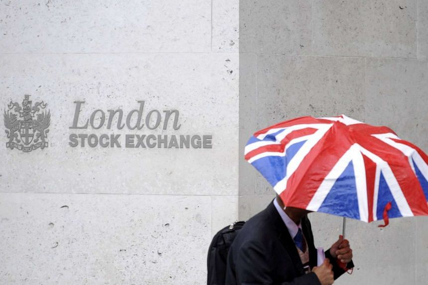 A worker shelters from the rain as he passes the London Stock Exchange.