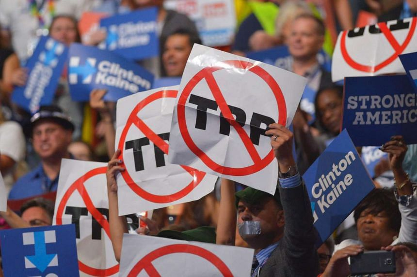 People hold signs against the Trans Pacific Partnership on Day 3 of the Democratic National Convention at the Wells Fargo Center, July 27 in Philadelphia, Pennsylvania.