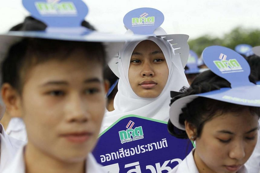 Thai students hold signs displaying messages calling on Thais to vote during a campaign held to promote the referendum on a new constitution at the Royal Plaza in Bangkok, Thailand on Aug 4, 2016.