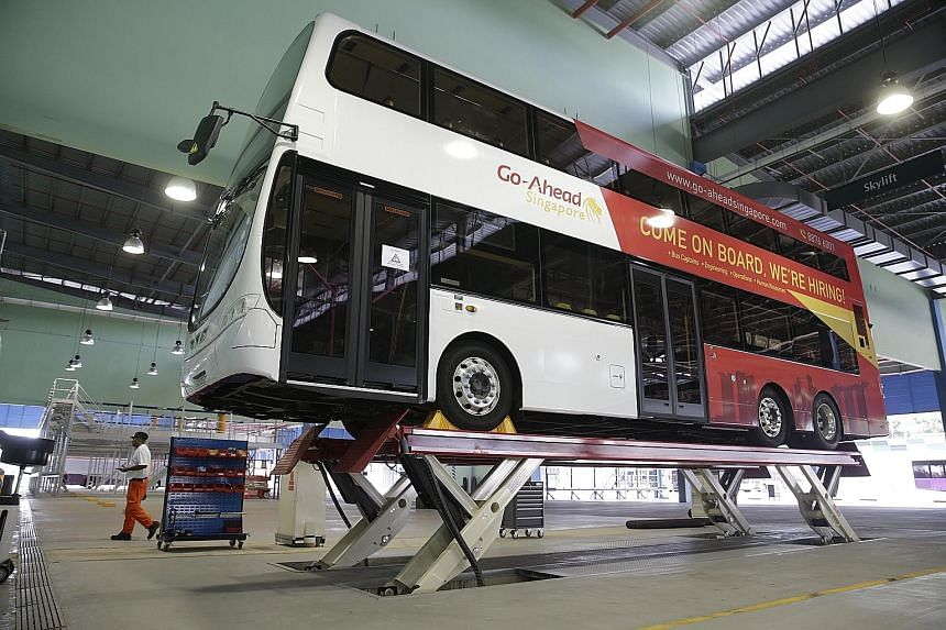 A Go-Ahead Singapore bus being hoisted in preparation for maintenance at the company's bus depot in Loyang. The operator is the second foreign bus company to join the industry under the bus contracting model, which aims to boost service standards.