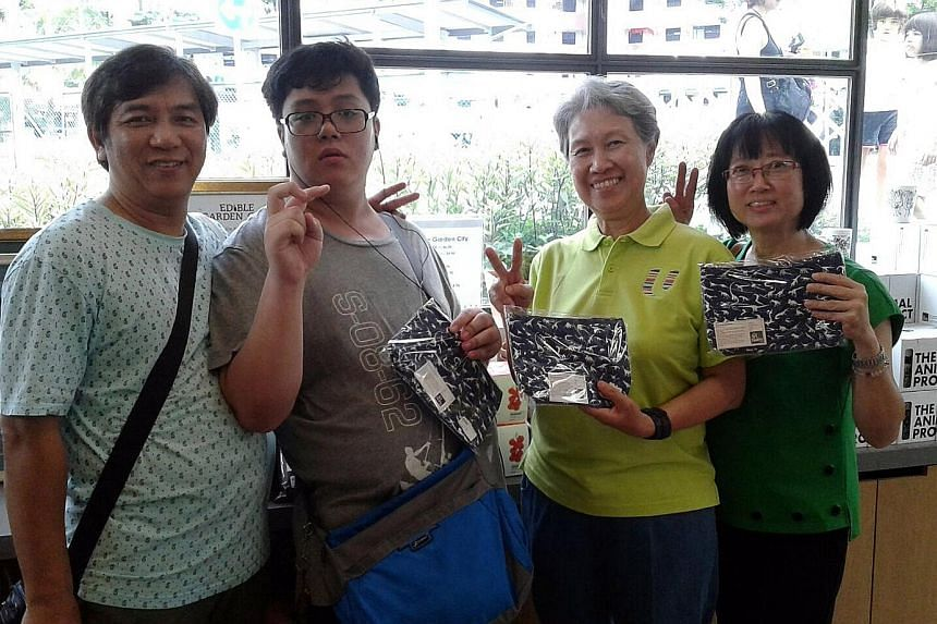Sheng Jie with his parents - taxi driver See Toh and manager Wendy Chua, 52 - and Mrs Lee at the Enabling Village in Lengkok Bahru with the dinosaur purses he designed.