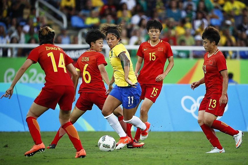 Cristiane (centre) surrounded by Chinese players during the first-round women's football match at the Olympic Stadium in Rio de Janeiro on Wednesday. She scored the final goal for Brazil in the 3-0 win.