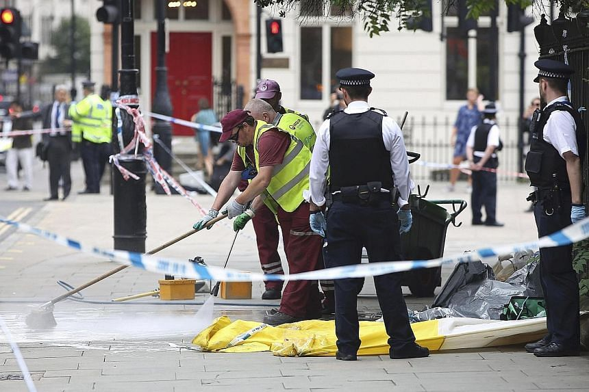 Police officers and cleaners at the scene of the knife attack in Russell Square in London yesterday. Police say that the suspect, a Norwegian man of Somali origin, seems to have chosen his victims at random.