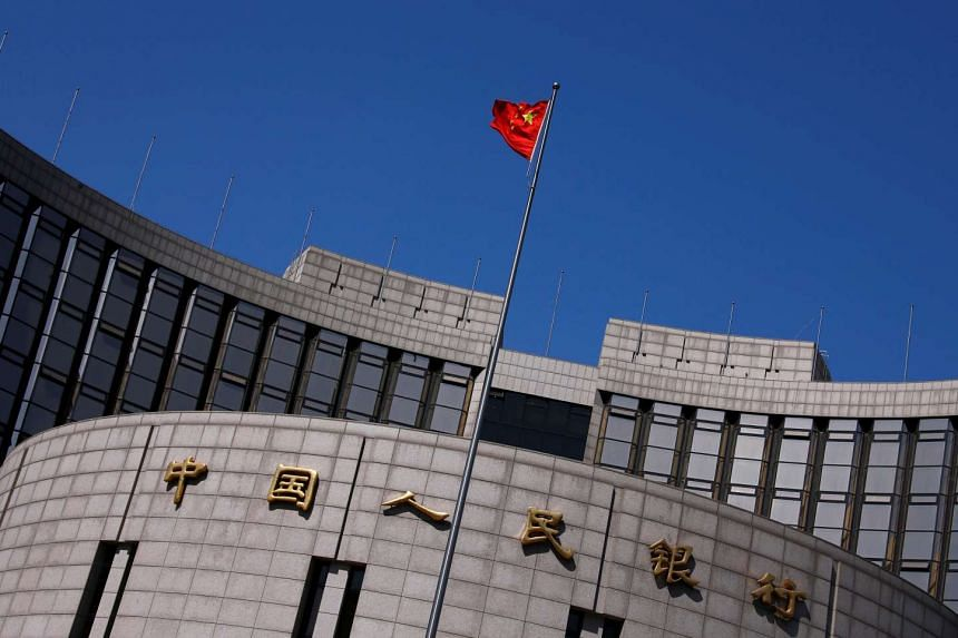 A Chinese national flag flutters outside the headquarters of the People's Bank of China in Beijing.