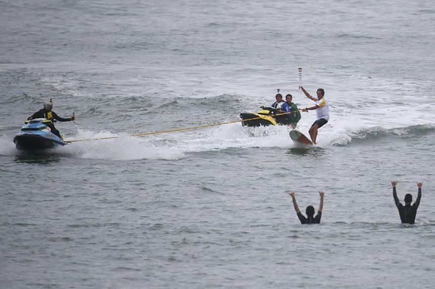Brazilian surfer Rico de Souza carries the Olympic torch as he surfs at Macumba beach in Rio.
