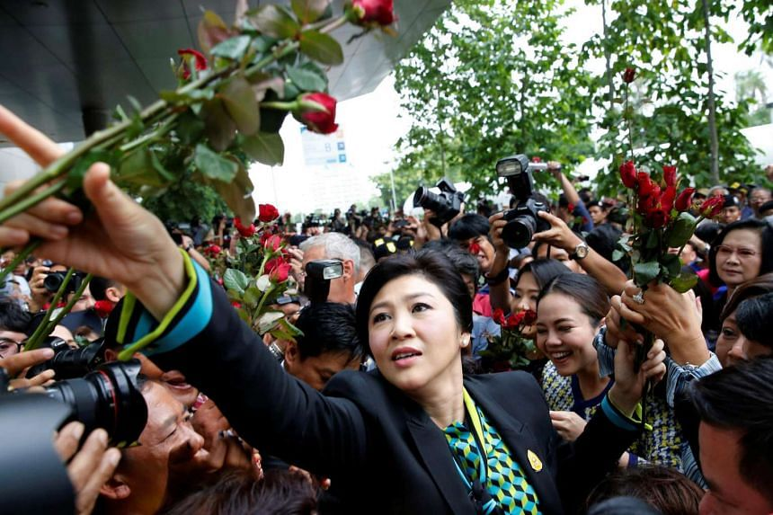 Former Thai Prime Minister Yingluck Shinawatra greets supporters as she arrives at the Supreme Court for a trial on criminal negligence looking into her role in a debt-ridden rice subsidy scheme during her administration, in Bangkok, Thailand on Aug