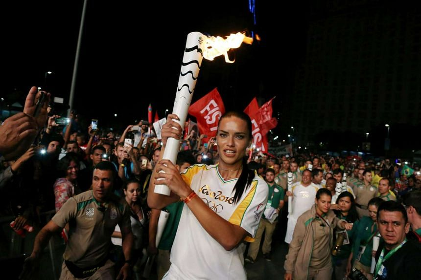 Supermodel Adriana Lima carries the Olympic torch in Maua Square in Rio de Janeiro.