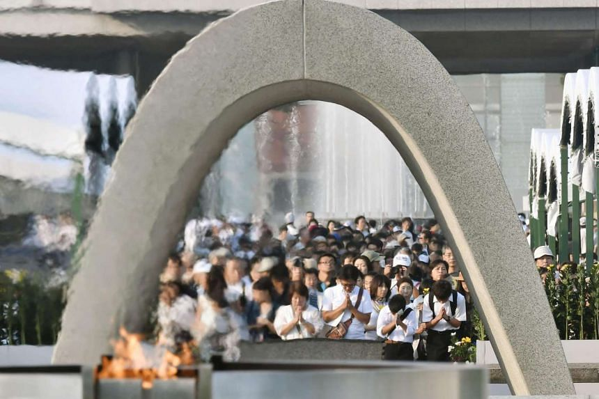 People pray in front of the cenotaph for the victims of the 1945 atomic bombing at Peace Memorial Park in Hiroshima, western Japan.