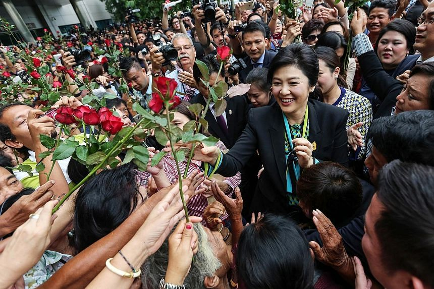 Former Thai PM Yingluck Shinawatra receiving flowers from supporters at Bangkok's supreme court yesterday. She is accused of dereliction of duty over her government's rice pledging scheme, which allowed farmers to sell their rice to the state at abou