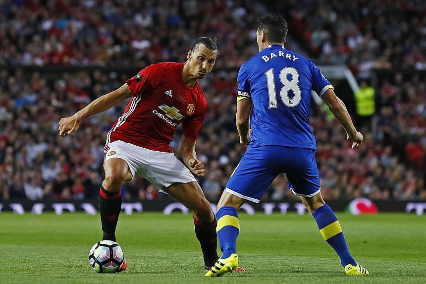 """Manchester United's Zlatan Ibrahimovic on the ball against Everton's Gareth Barry in Wayne Rooney's testimonial on Wednesday. Manager Jose Mourinho describes the newly joined Swede as a """"super striker"""", and anticipates the arrival of one more very """"g"""