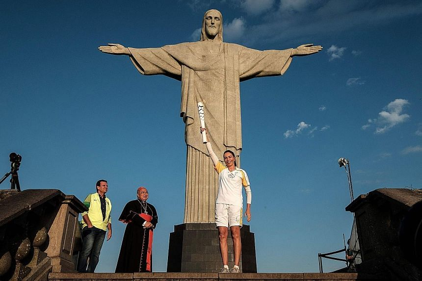 Left: Olympic torch bearer and former Brazilian volleyball player Maria Isabel Barroso Salgado holds the torch of the Rio 2016 Olympic Games as Mayor Eduardo Paes (extreme left) and Rio Archbishop Orani Tempesta look on, in front of the landmark stat