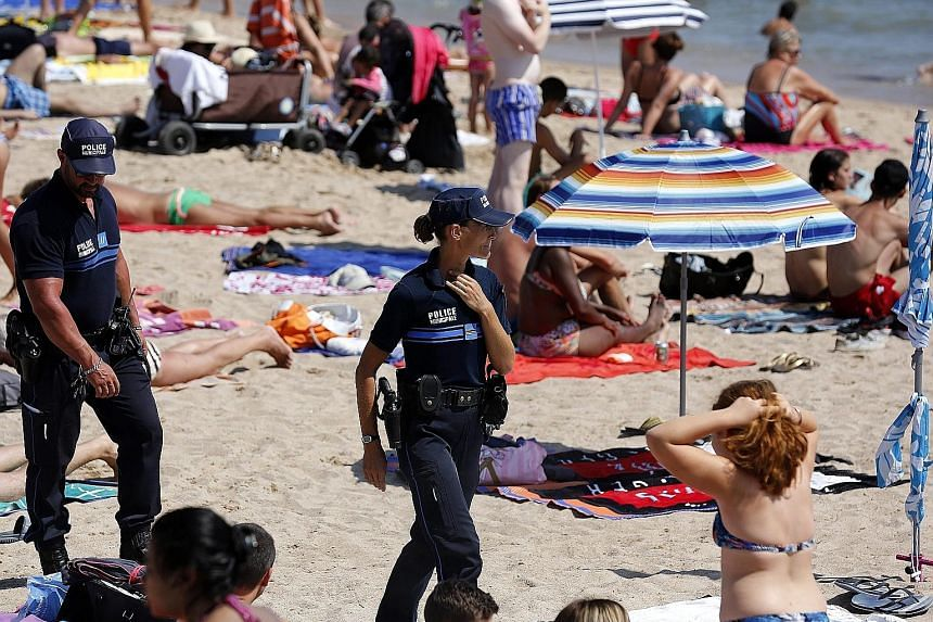 French police officers patrolling a Cannes beach. Extra troops have been deployed in holiday resorts to protect France's valuable tourism industry.
