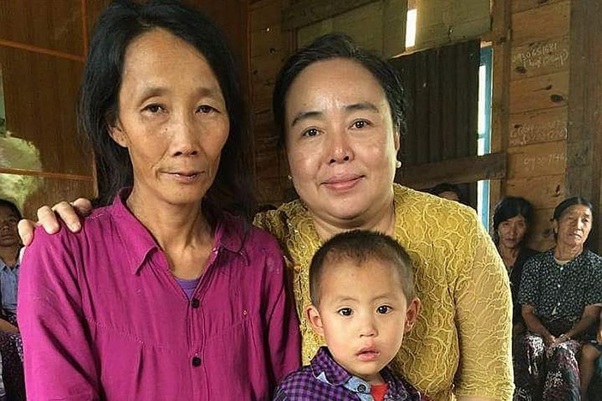 Above: Mr Pau has erected a cross in his village to remember his sister, Ms Piang, who was allegedly murdered by her employers last month. Left: Ms Piang leaves behind a young son, Mung Lam Tuang, seen here with her sister (far left) and a volunteer