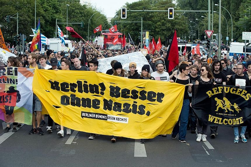"""Pro-refugee supporters with a banner that reads """"Berlin! Better without Nazis"""" during a demonstration last month. Dr Merkel's open-door refugee policy has come under attack from critics."""