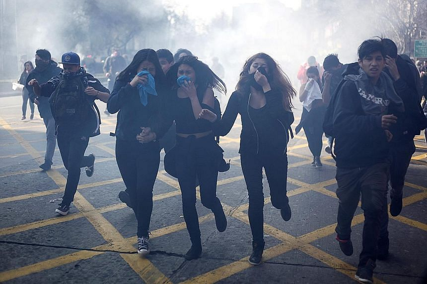 Chilean student protesters covering their faces after police fired tear gas during a clash in Santiago de Chile on Thursday. Thousands of students took to the streets in the capital and other cities in Chile to denounce a proposed education overhaul