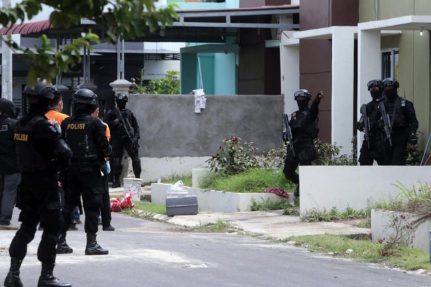 An Indonesian anti-terror police squad searches for evidence during a raid at a residential area in Batam Center, Batam, Riau Islands, Indonesia, on August 5.