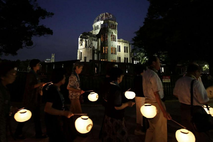 People holding paper lanterns march around the Atomic Bomb Dome (top) to comfort souls of the victims killed by the atomic bombing during World War II in 1945, at Hiroshima Peace Memorial Park in Hiroshima, western Japan, on August 5.