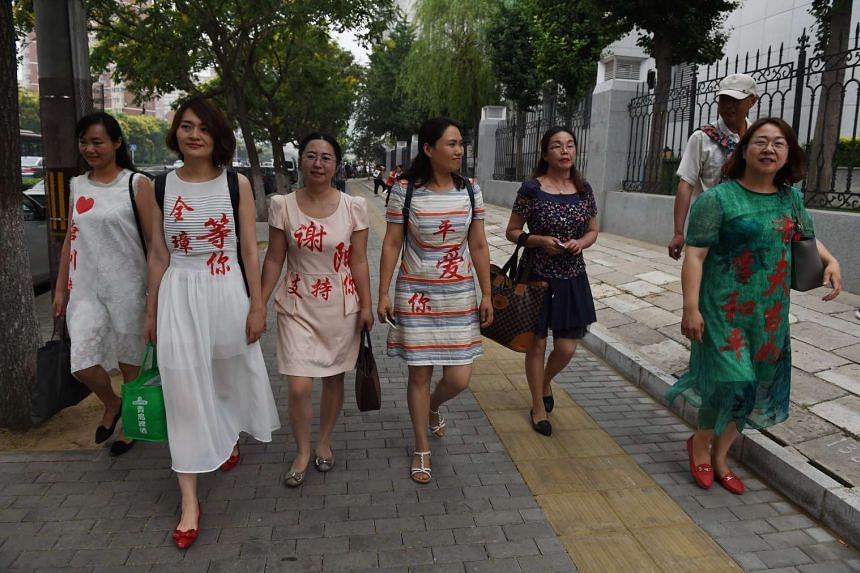 The wives of human rights lawyers detained in 2015 wearing the names of their husbands after attempting to hand in a formal complaint on July 4, 2016.