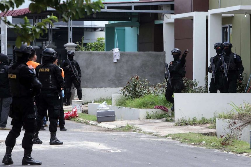 An Indonesian anti-terror police squad searches for evidence during a raid at a residential area in Batam Center on Aug 5, 2016.