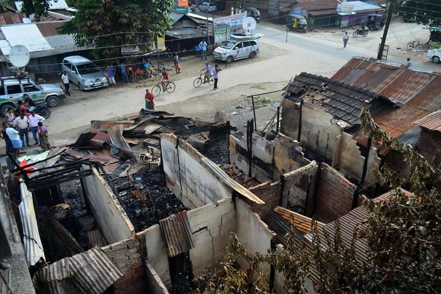 Bystanders gather near burnt out shops following an attack on a market at Balajan Tinali on Aug 6, 2016.
