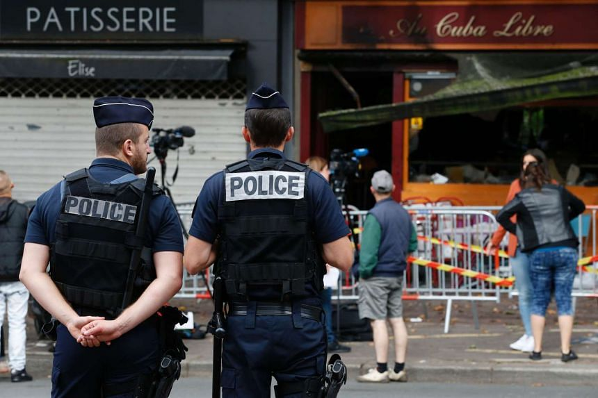 Police officers stand outside the damaged Au Cuba Libre bar in Rouen, northern France, on Aug 6, 2016.