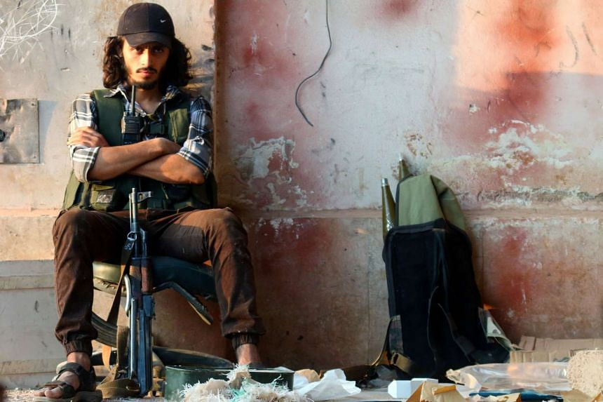 A rebel fighter sits with his weapon in the artillery academy of Aleppo, Syria, Aug 6, 2016.