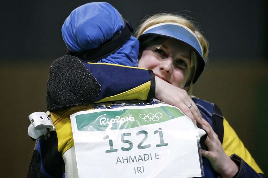 Virginia Thrasher of the USA is congratulated by Elaheh Ahmadi of Iran after winning the gold medal for the Rio 2016 Olympic Games women's 10m air rifle finals on Aug 6, 2016.