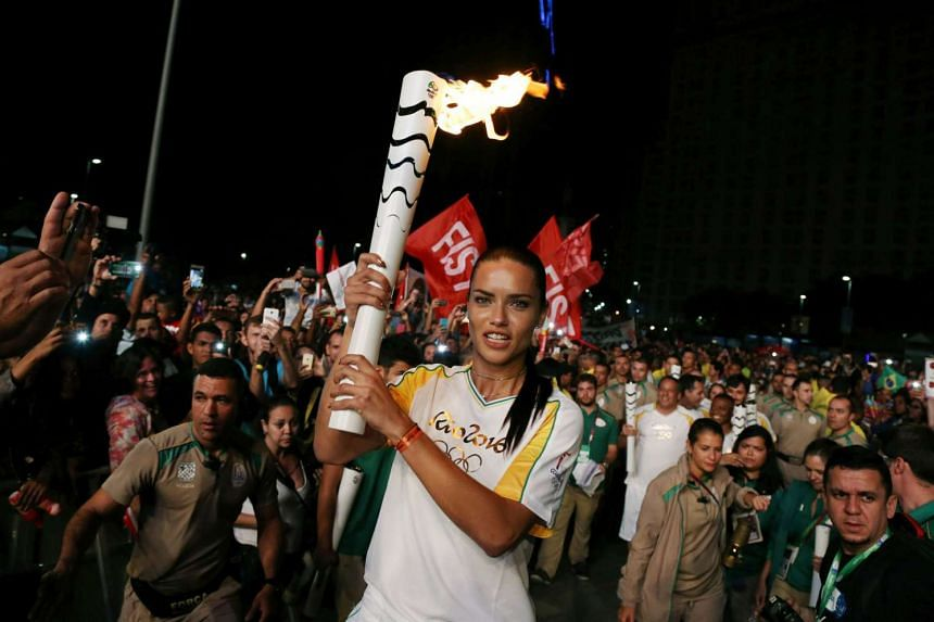 Model Adriana Lima carries the Olympic torch in Maua Square in Rio de Janeiro, Brazil, Aug 4, 2016.