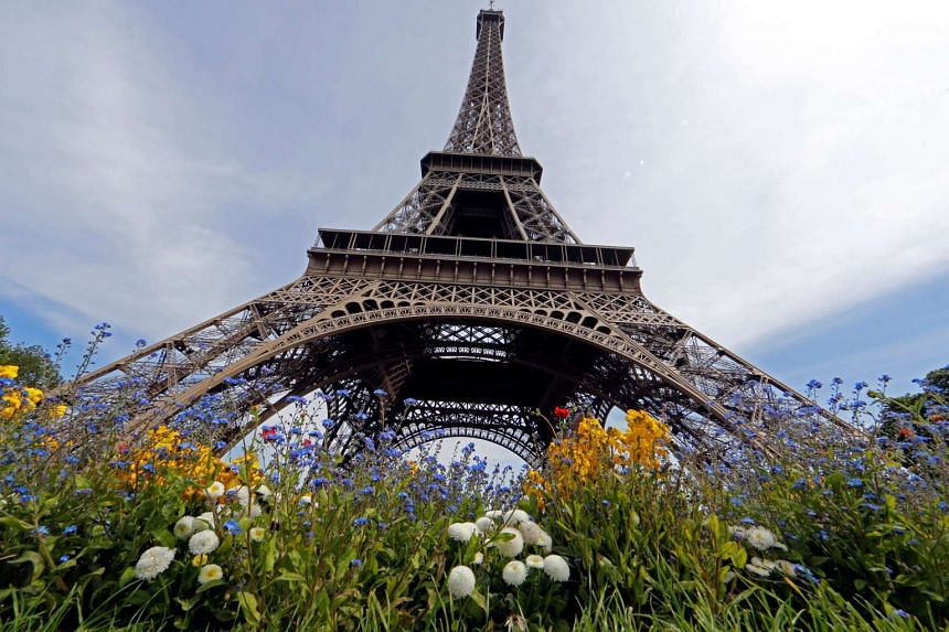 Flowers are seen in front of the Eiffel Tower on a sunny spring day in Paris, France, May 8, 2016.
