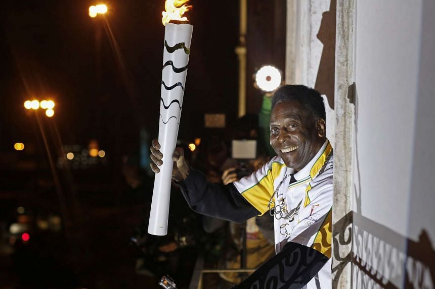 Pele holds the Olympic flame at the Pele Museum in Santos, Sao Paulo State, Brazil, on July 22, 2016, in a handout photo.