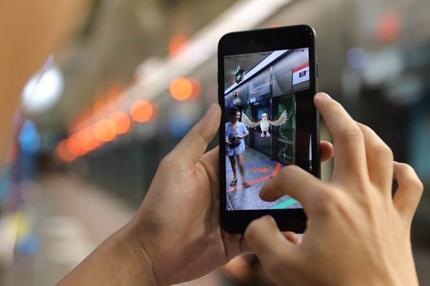 A Pokemon Go player trying out the game at Orchard MRT station.