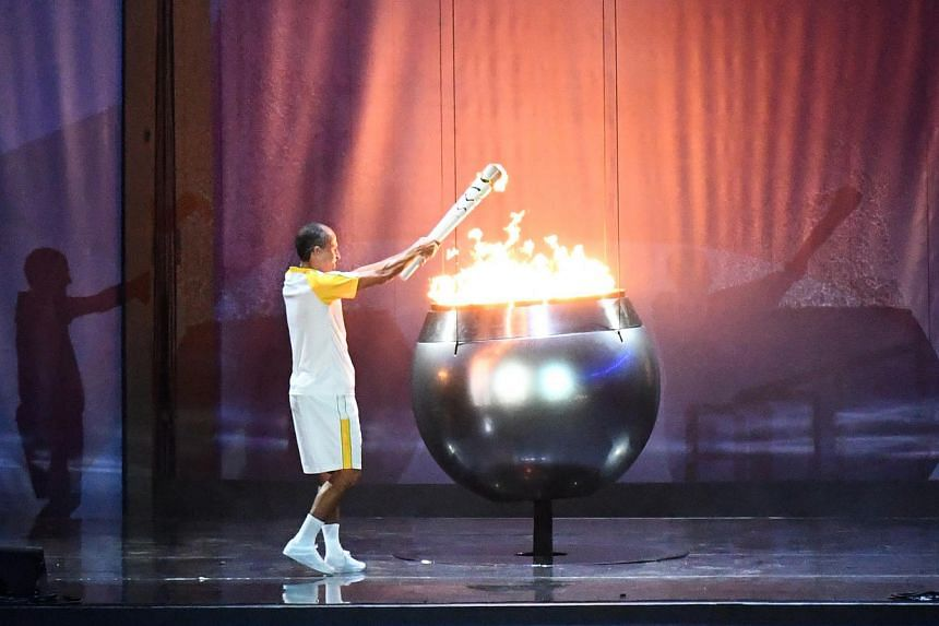 Former Brazilian athlete Vanderlei Cordeiro lights the Olympic cauldron with the Olympic torch.