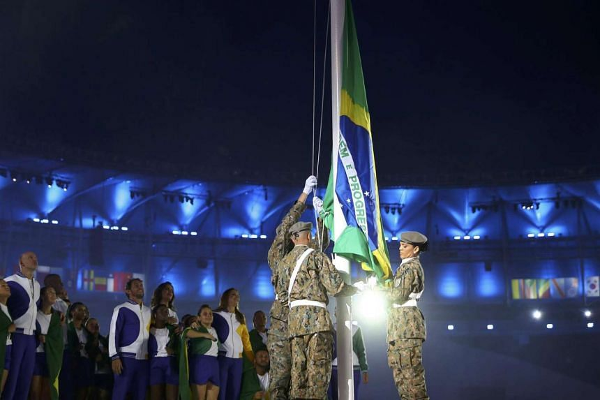 The Brazilian national flag is raised during the opening ceremony.