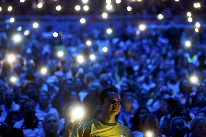 Spectators use their mobile phones for illumination.