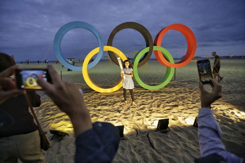 Visitors taking pictures in front of the Olympic rings at Copacabana beach.