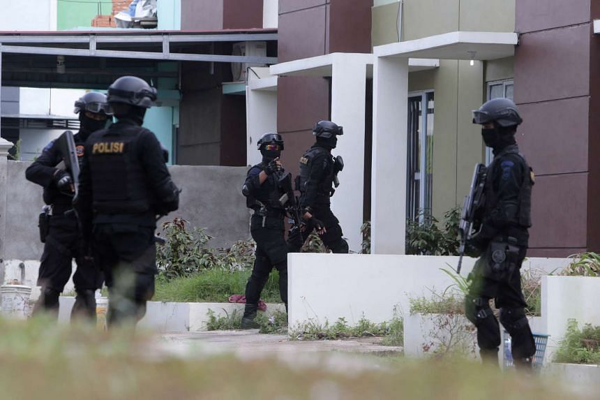 Indonesian anti-terror police entering a building during a raid in Batam on Aug 5, 2016.
