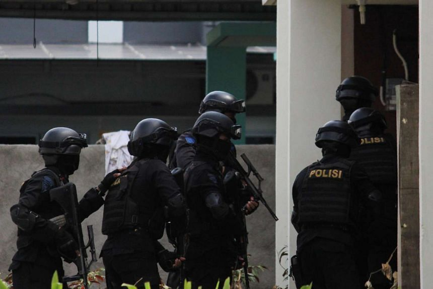 Indonesian anti-terror police conduct a raid at a house in Batam on August 5.