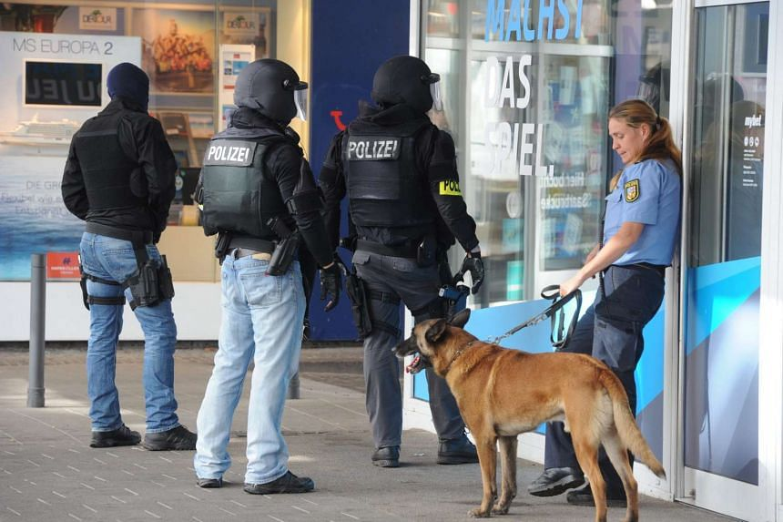 Riot police wait out the front of a restaurant in the center of Saarbruecken where an injured and armed man has barricaded himself in, in Germany on Aug 7, 2016.