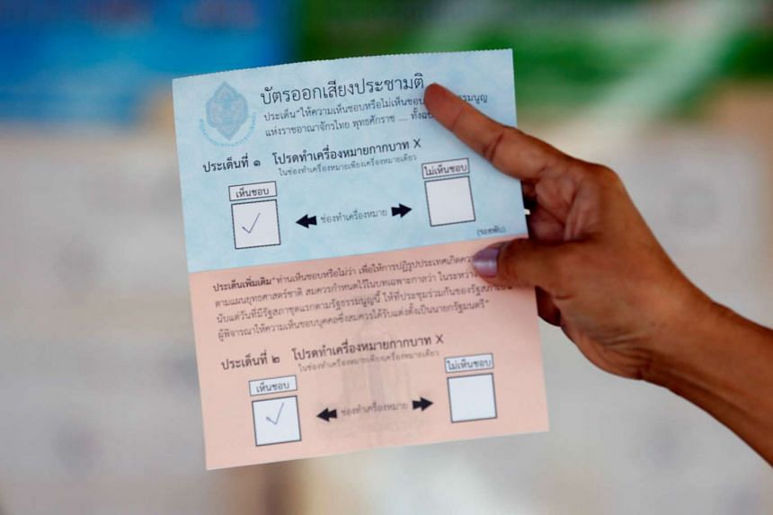 An election commission official displays a ballot paper to the media while counting votes during a constitutional referendum vote at a polling station in Bangkok on Aug 7, 2016.