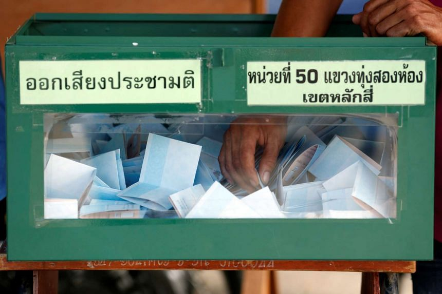 An election commission official holds a ballot paper from a ballot box while counting votes during a constitutional referendum vote at a polling station in Bangkok on Aug 7, 2016.