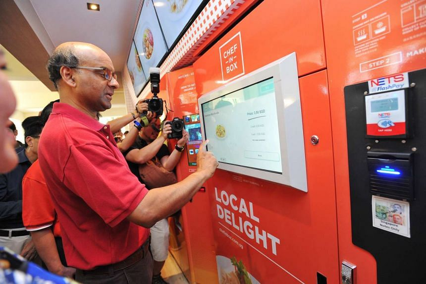 """DPM Tharman Shanmugaratnam looking at the menu of a """"Chef-in-Box"""" hot food machine at VendCafe on Aug 7, 2016."""