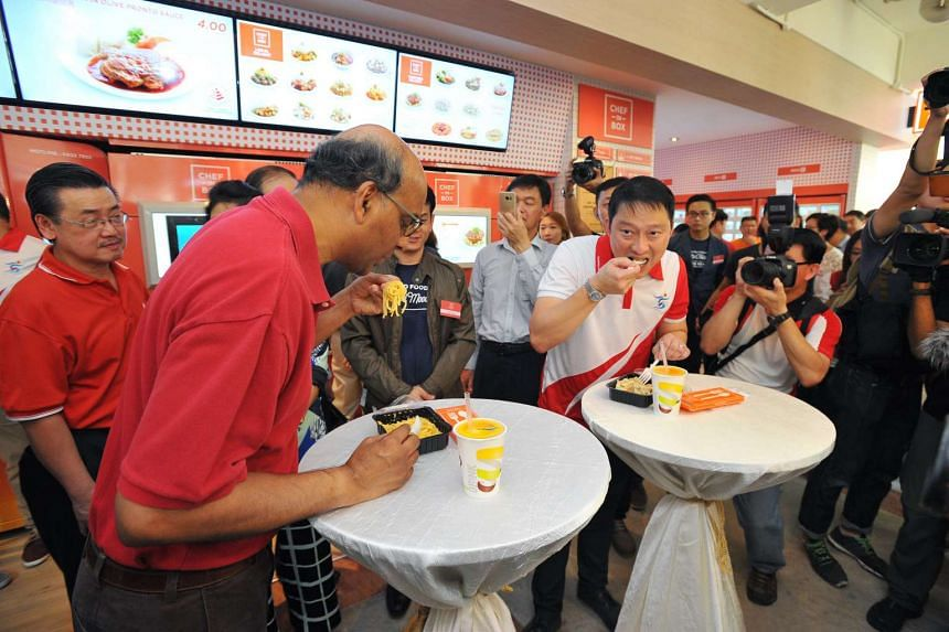 DPM Tharman Shanmugaratnam and Sengkang West MP Lam Pin Min eating hot food from a vending machine, at VendCafe on Aug 7, 2016.